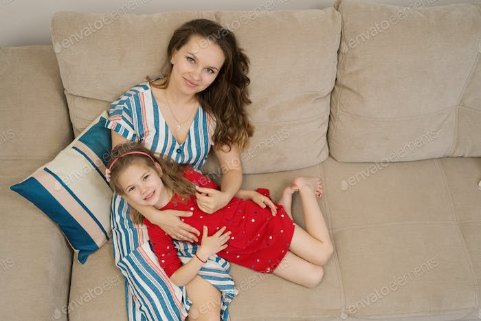 Mother and daughter portrait lying on sofa