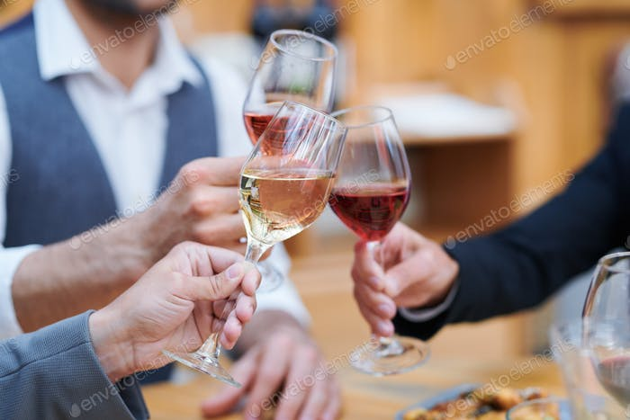 Three humans clinking with wineglasses of varoius sorts of wine