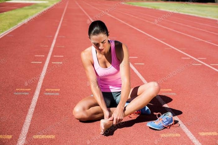 Sportlerin mit Fußschmerzen auf Laufbahn