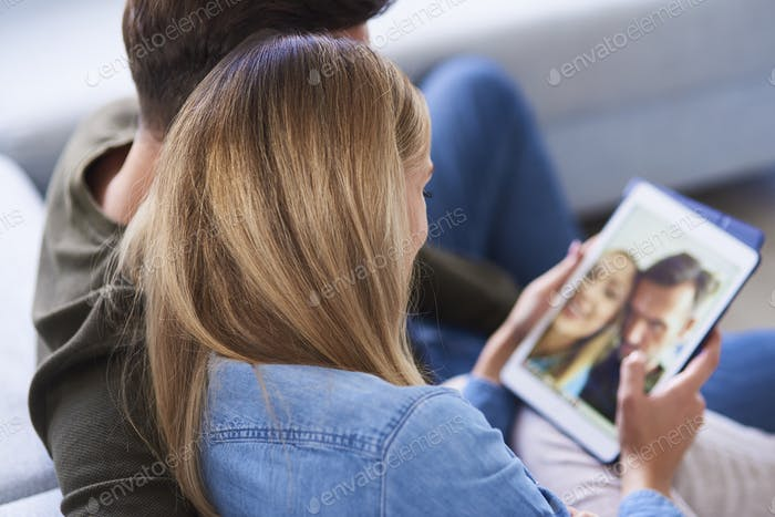 Close up of couple embracing and using a tablet