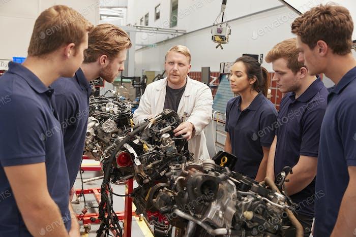 Mechaniker zeigt Teile eines Motors für Auszubildende, Nahaufnahme