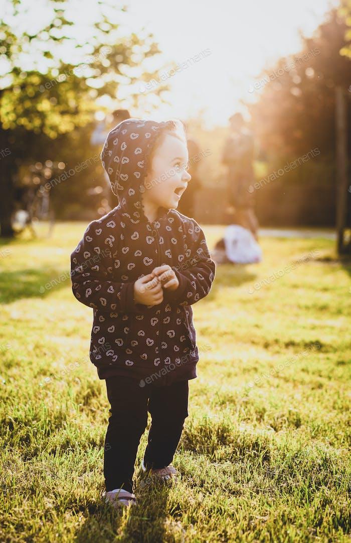 Toddler girl having fun in the park.