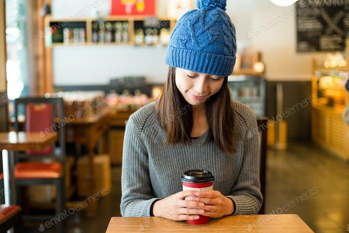 Woman holding coffee in coffee shop