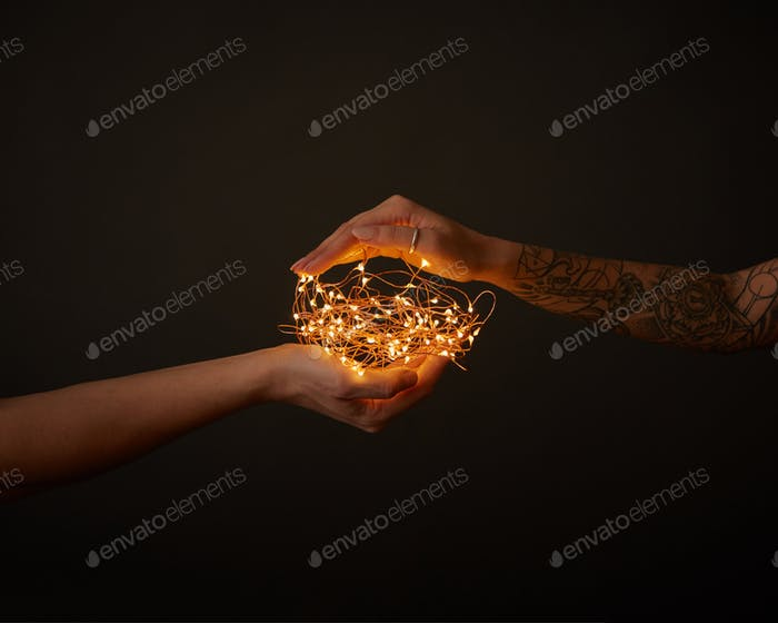 A bunch of Christmas garlands holds a male and female hand with a tattoo on a black background with