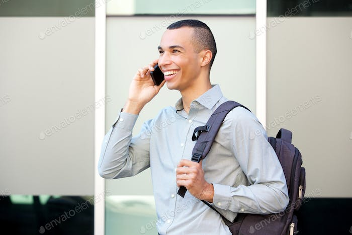happy young businessman walking and talking on mobile phone