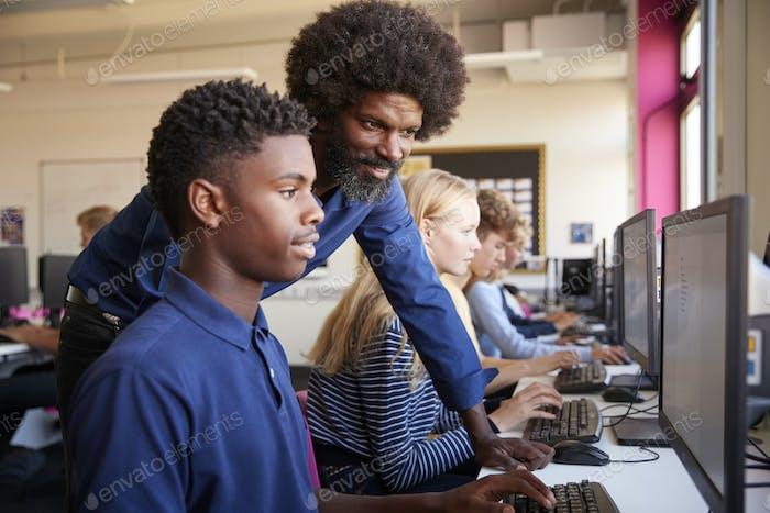 Teacher Helping Teenage Male High School Student Working In Computer Class