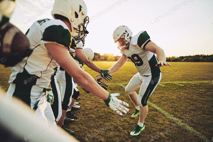 American football player low fiving his teammates after a game