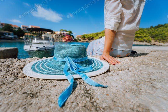Female tourist sitting on the pier with blau sun hat at her side in Assos village in front of