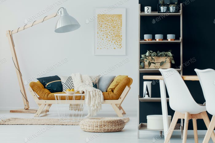 Pouf and table in front of mustard couch and wooden lamp in flat