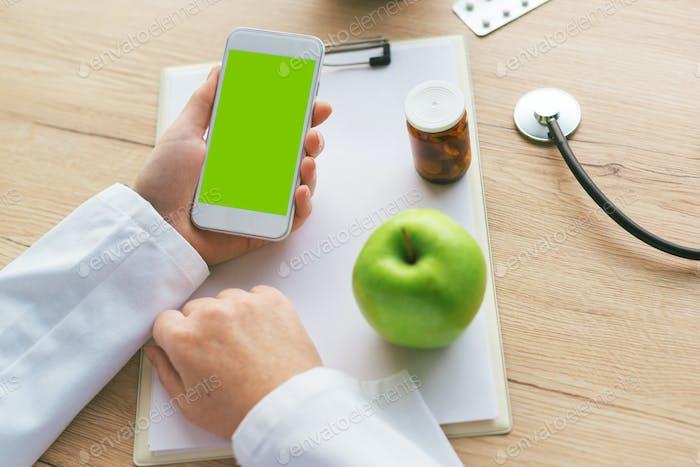 Doctor advising apple instead of pills and antibiotics