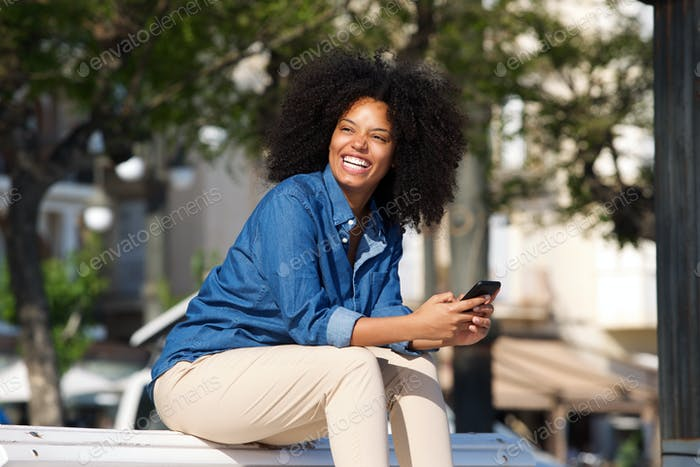 Cheerful woman sitting outside with mobile phone