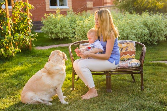 Mutter hält Baby Sohn und spielen mit Labrador Hund im Park