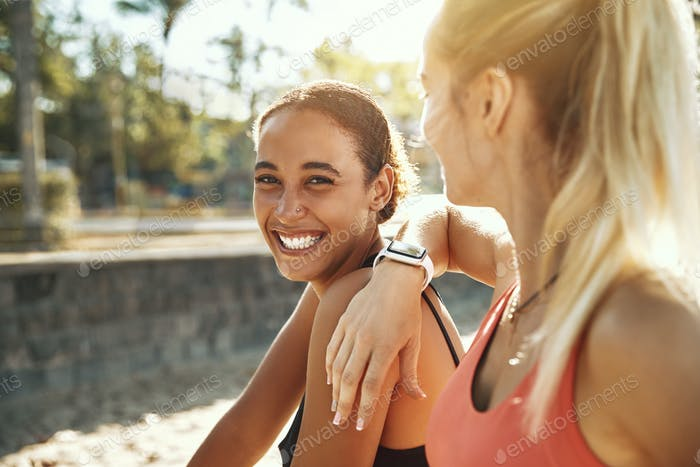 Two laughing young women taking a break from exercising outside