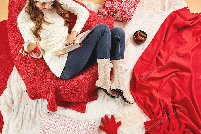 Girl dressed in white knitted sweater, jeans and knitted socks lies on red-white blankets and