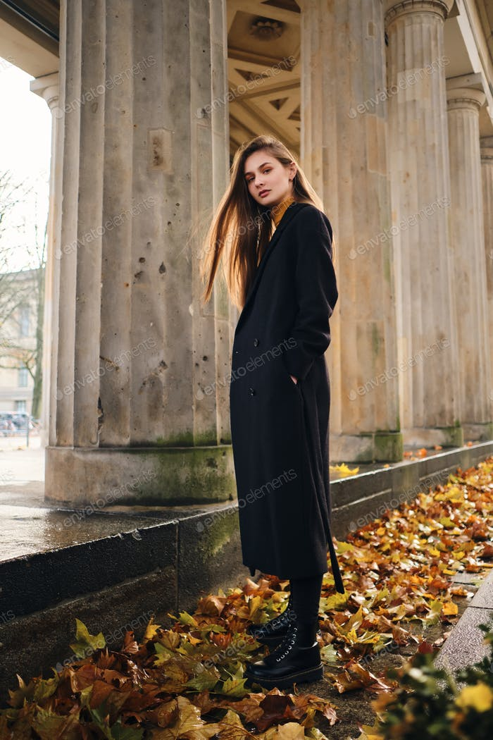 Attractive stylish girl in coat confidently looking in camera on street