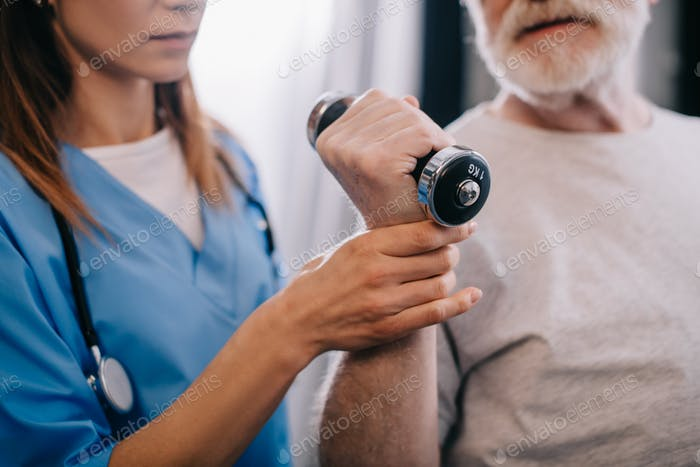 Old man with dumbbell and nurse during physiotherapy