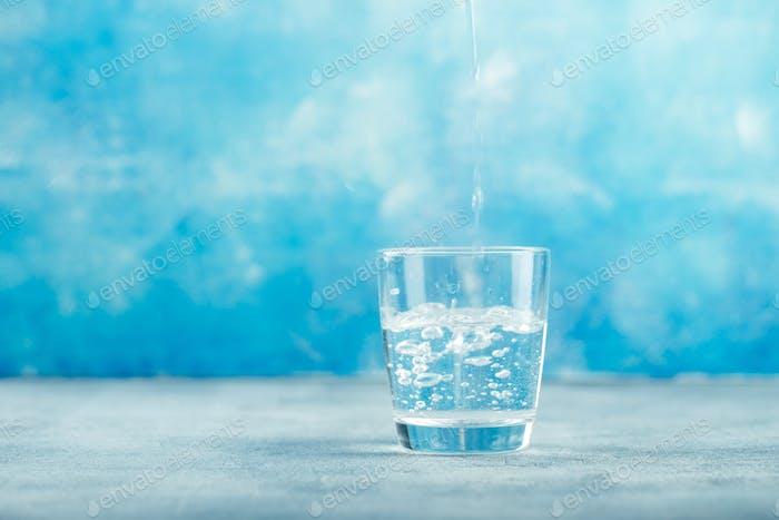 Wasser aus der Flasche in Glas gießen
