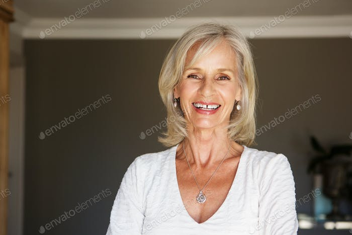 happy older woman standing inside home