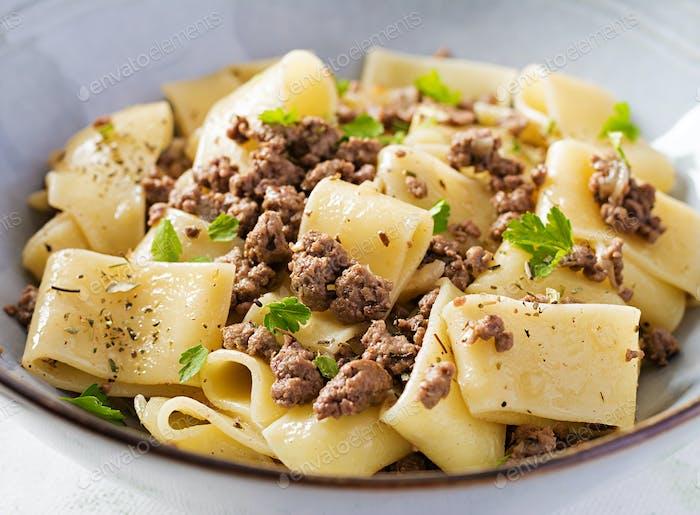 Pasta Calamarata mit Hackfleisch in blauer Schüssel. Italienische Küche.