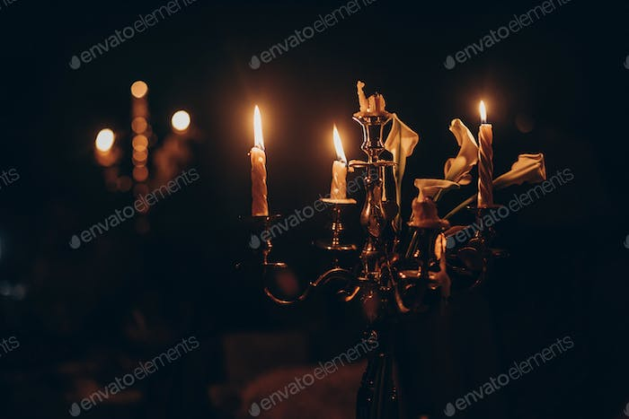 candles burning on golden candlestick in church