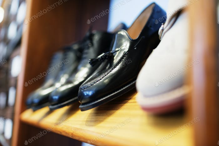 Formal shoes arranged in shelf at clothing store