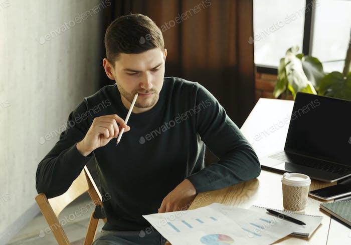Millennial Guy Thinking On Business Startup Sitzen In Coworking Workspace