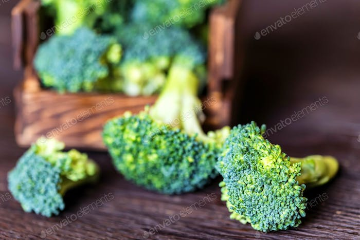 Fresh broccoli in wooden box on wooden surface