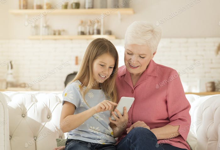 Mature woman playing video games on smartphone with her granddaughter at home