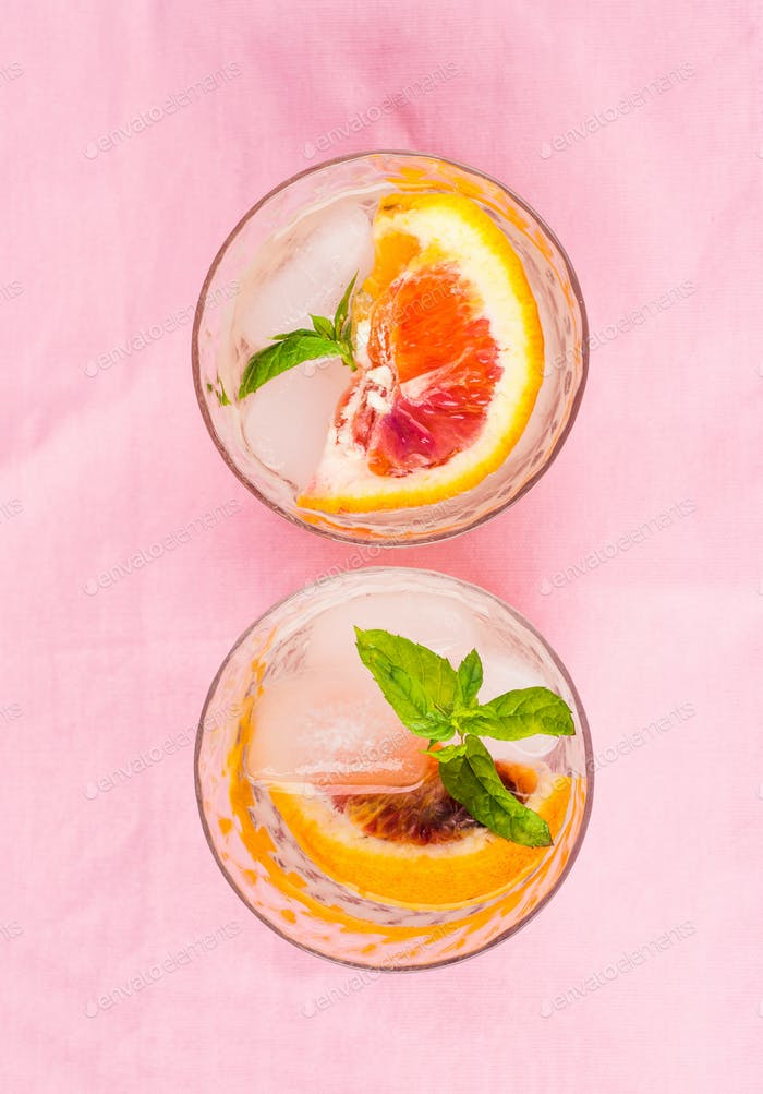Summer iced citrus drink with mint on pink napkin