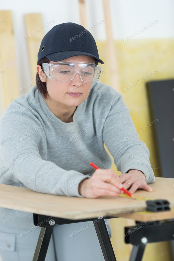 portrait of happy female woodworker drafting new project at workshop