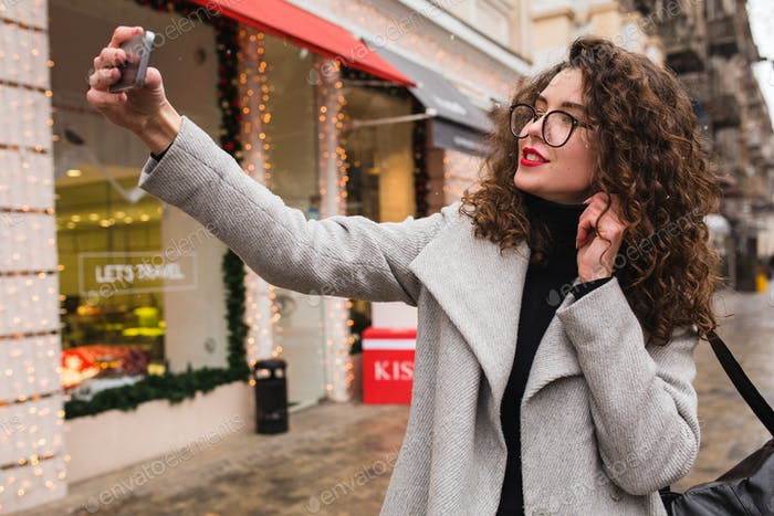 joven hermosa mujer caminando en la calle de la ciudad en abrigo gris