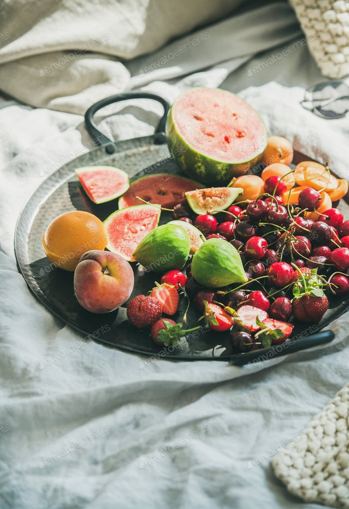 Tray full of fruit over light blanket background, copy space