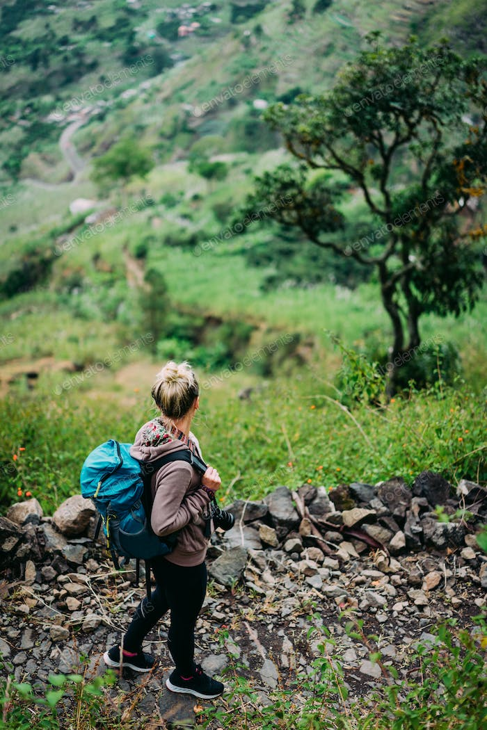 Female hiker with backpack walking down cobbled path to the lush green Paul valley. Santo Antao Cape