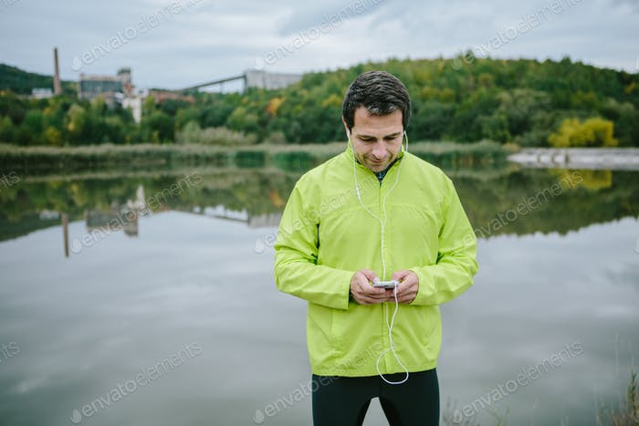 Runner at the lake with smart phone listening music