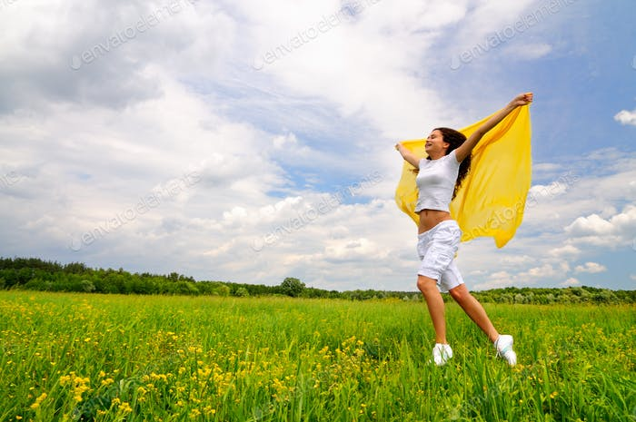 Young smiling woman standing with silk shawl in meadow