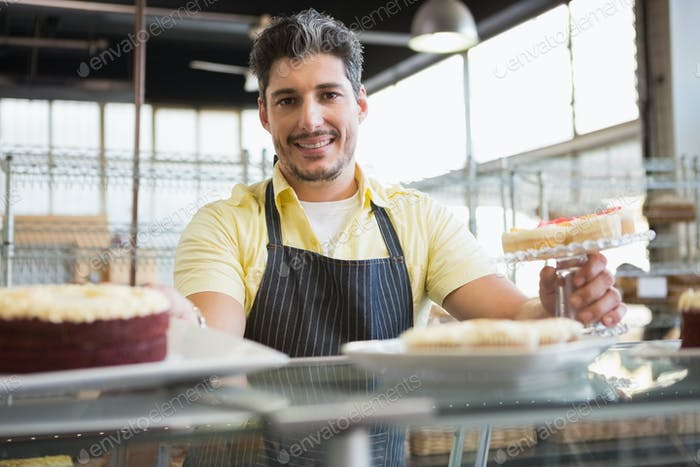 Attractive worker in apron posing  at the bakery