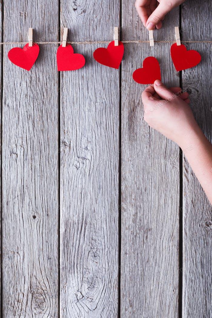 Valentine day handmade background, paper hearts border on wood