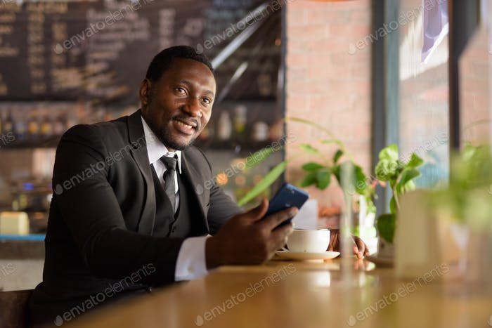 Happy bearded African businessman thinking while using phone at the coffee shop