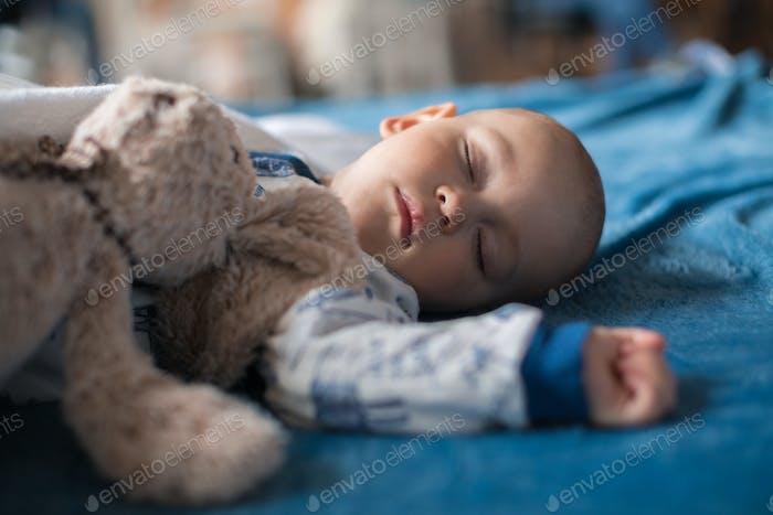 Cute baby boy sleeping with teddy bear