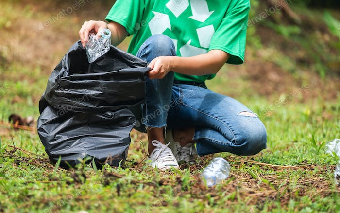 a female activist picking up garbage plastic bottles into a plastic bag