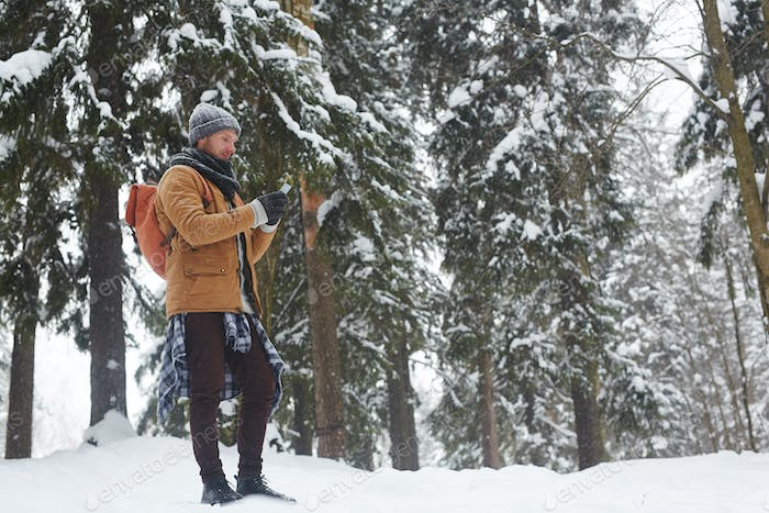Young hiker using gadget in forest