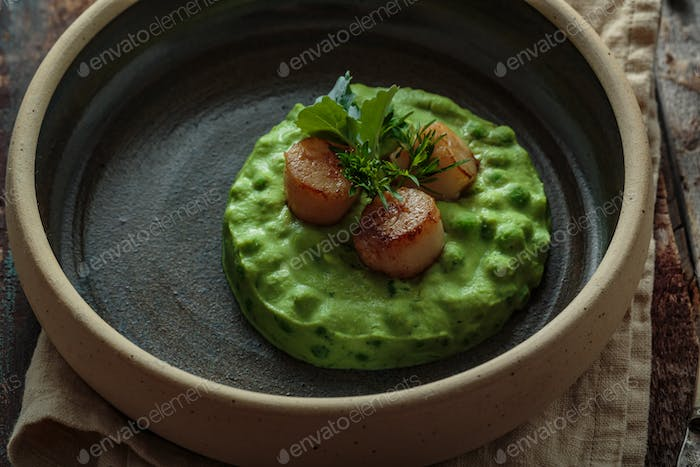 Close view of Seared Scallops with pea puree on a plate