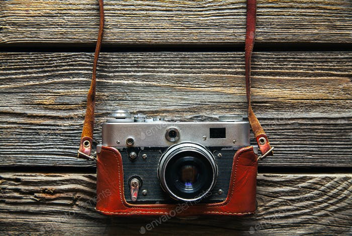 Thumbnail for Retro camera on wood table background, vintage color tone