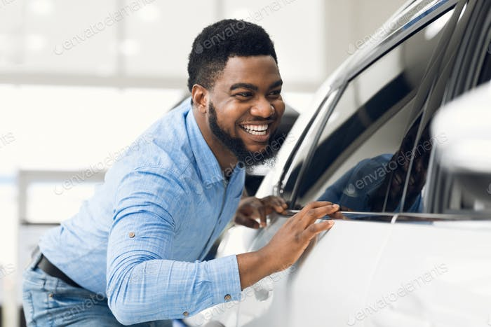 Afrikanischer Guy Berühren sein neues Fahrzeug im Händler-Showroom