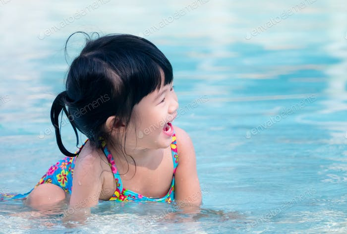 Happy asian kid laugh while playing in the swimming pool