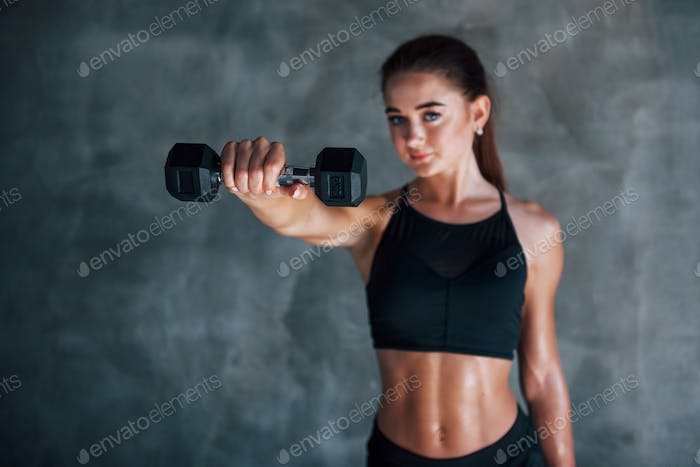 Young fitness woman is in the gym near wall with dumbbells in hands