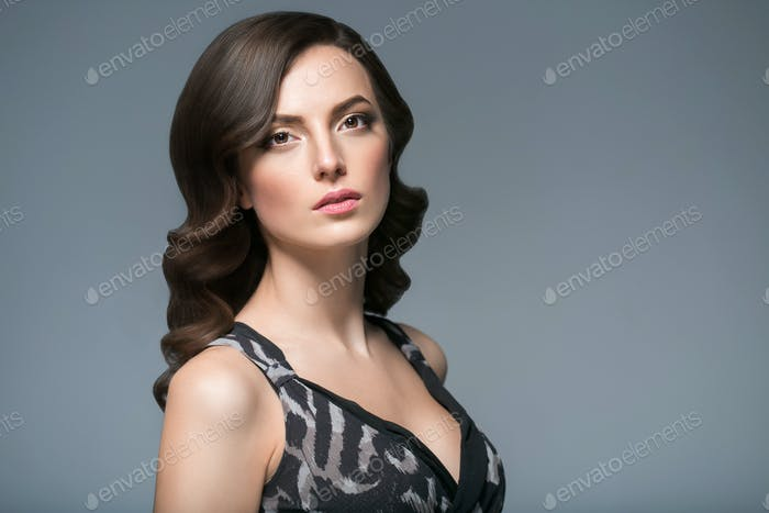 Serious woman with curly hairstyle portrait gray background. Female young beauty model girl face