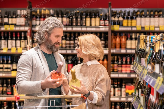 Happy aged couple choosing wine while standing among shelves with alcohol