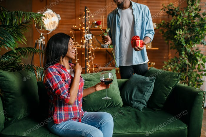 Black man with red rose and gift behind his woman