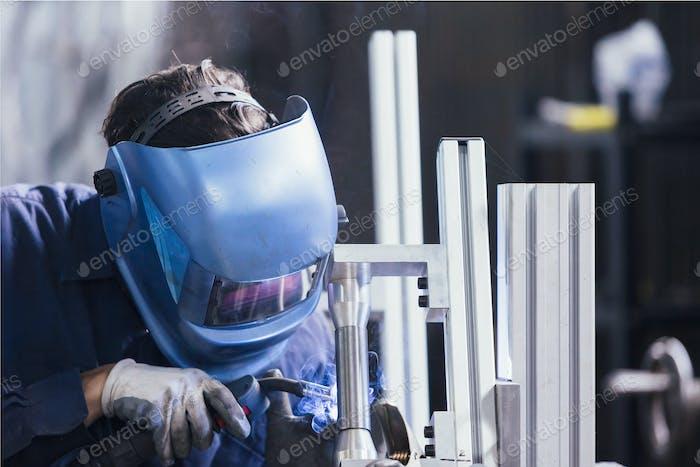 Unrecognizable worker welding with metal detail